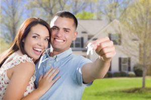 A young couple holding the keys to their new home